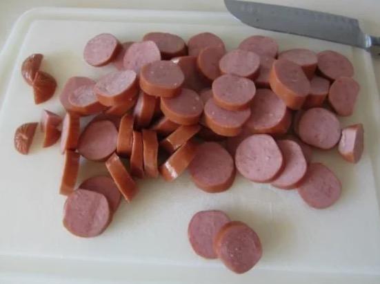 Вареную колбасу, сосиски или ветчину очищаем от шкурки и мелко нарезаем