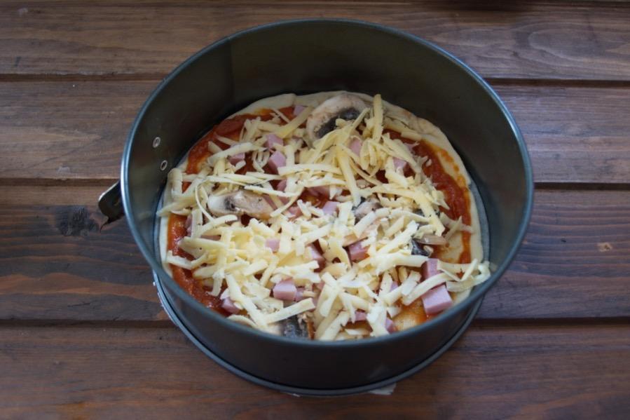 В последнюю очередь покрываем пиццу натертым на крупной терке сыром